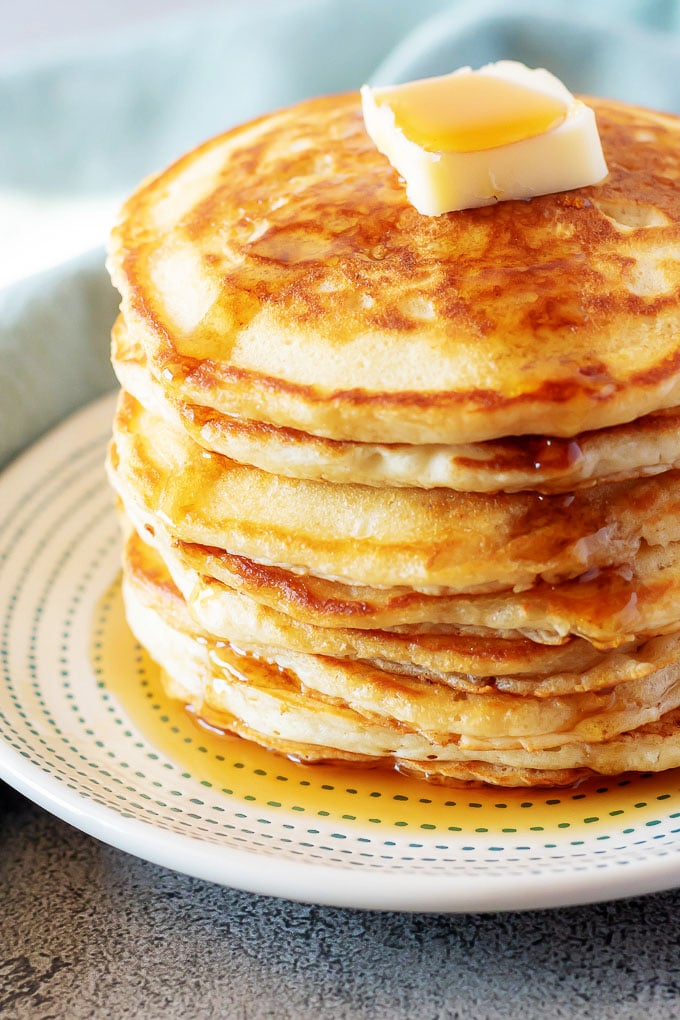 A close-up photo of the fluffy American pancakes served on a white plate and topped with butter and maple syrup.