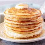 A tall stack of fluffy American pancakes on w white plate topped with butter.