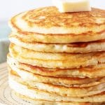 A large photo of the finished fluffy American pancakes topped with butter and served on a white plate.