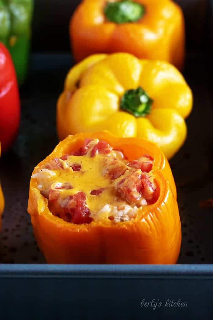 Cooked ground turkey stuffed peppers covered with melted cheese and tomatoes.