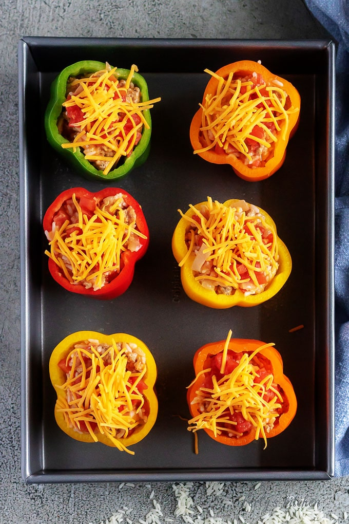 Arial view of uncooked prepared stuffed peppers in a baking dish.