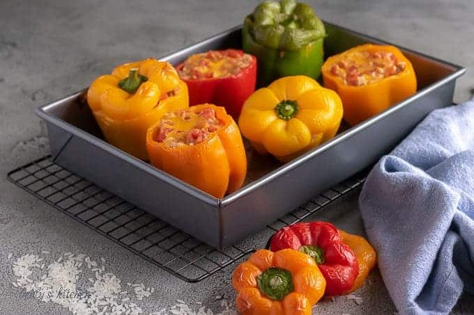 Ground Turkey Stuffed Peppers in a baking dish next to scattered rice and a blue linen.