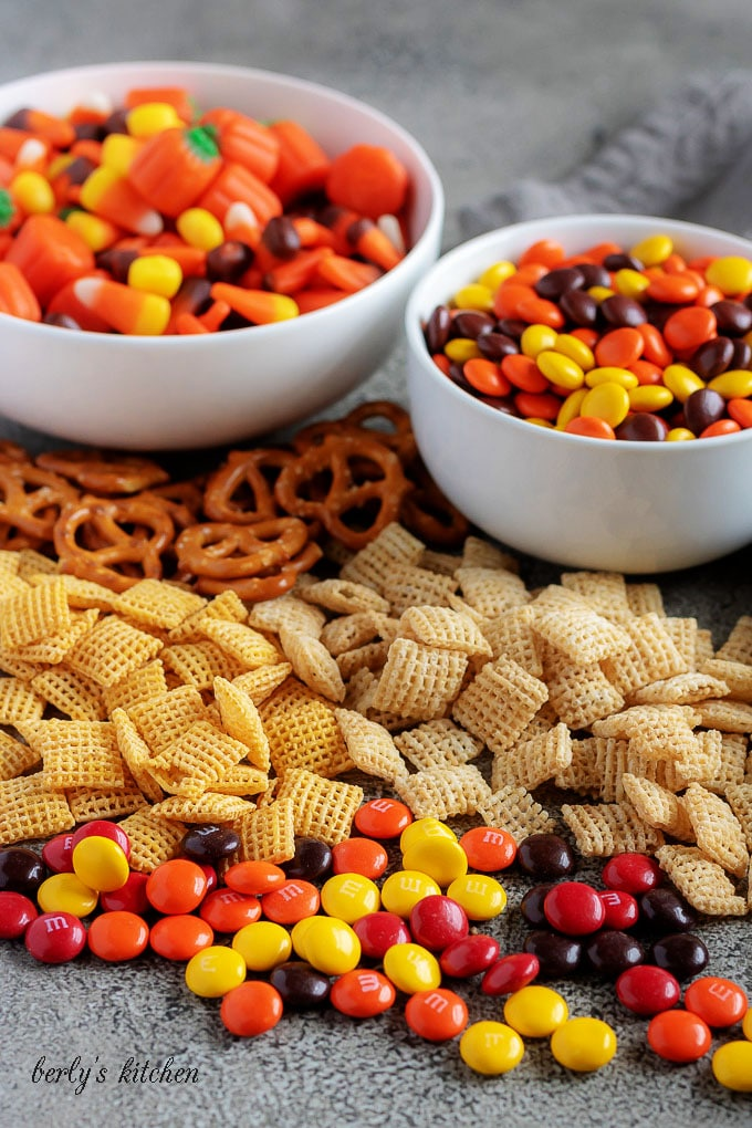 An angled photo o fthe party mix ingredients, like Chex cereal, M&M's, Reese's pieces, and pretzels.