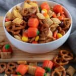 The party mix is completed and being served in a white bowl with extra party mix sprinkled around it as a prop.