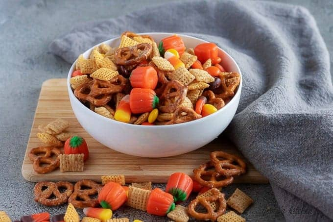 A party mix, loaded with candy corn, pretzels, and cady pumpkins, served in a white bowl.