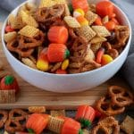 A close-up photo of the candy and pretzel filled party mix, served in a white bowl.