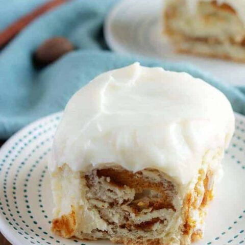 A picture of a finished pumpkin cinnamon roll sitting a white plate and topped with the frosting.