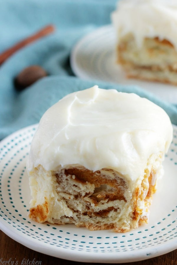 A large photo showing the finished pumpkin pie cinnamon rolls topped with a rich maple frosting and sitting on a white plate.