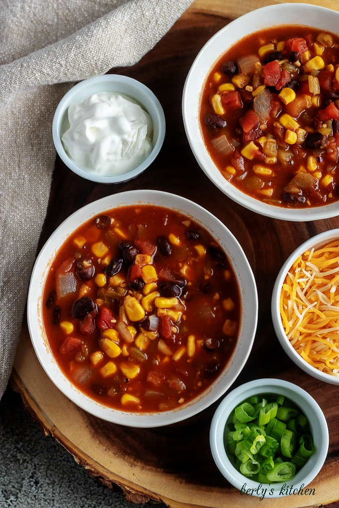 A close-up photo of the finished black bean chili, served in white bowls, sitting on a wooden decorative tray.
