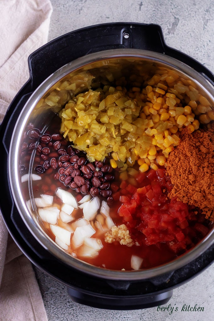 The top-down picture shows the black bean ingredients inside of the pressure cooker, ready to be sealed and cooked.
