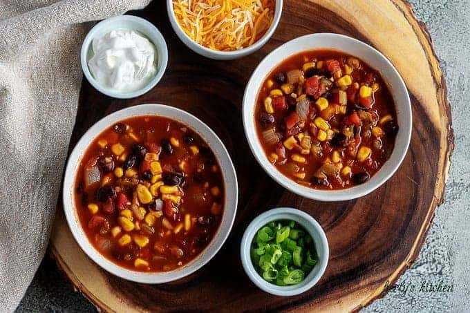 An aerial photo of the black bean chili served cheese, green onions, and sour cream on the side.