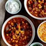 The picture is of the finished black bean chili, served in white bowls with sides of green onions, cheese, and sour cream as toppings.
