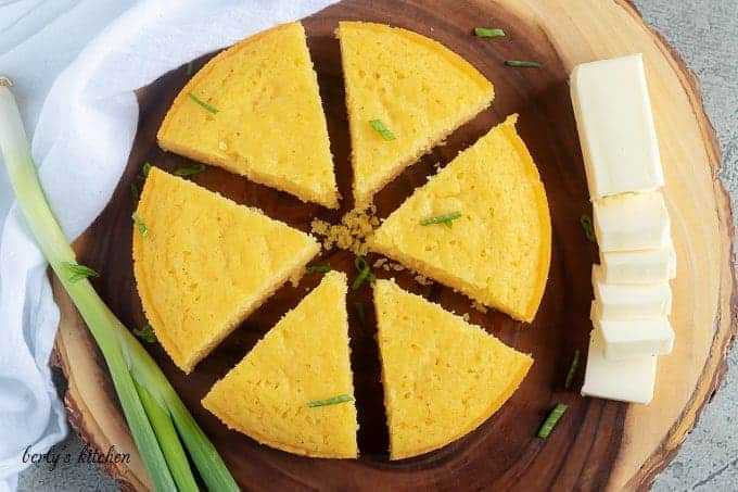 Arial view of buttermilk cornbread on a cutting board with green onion and butter.