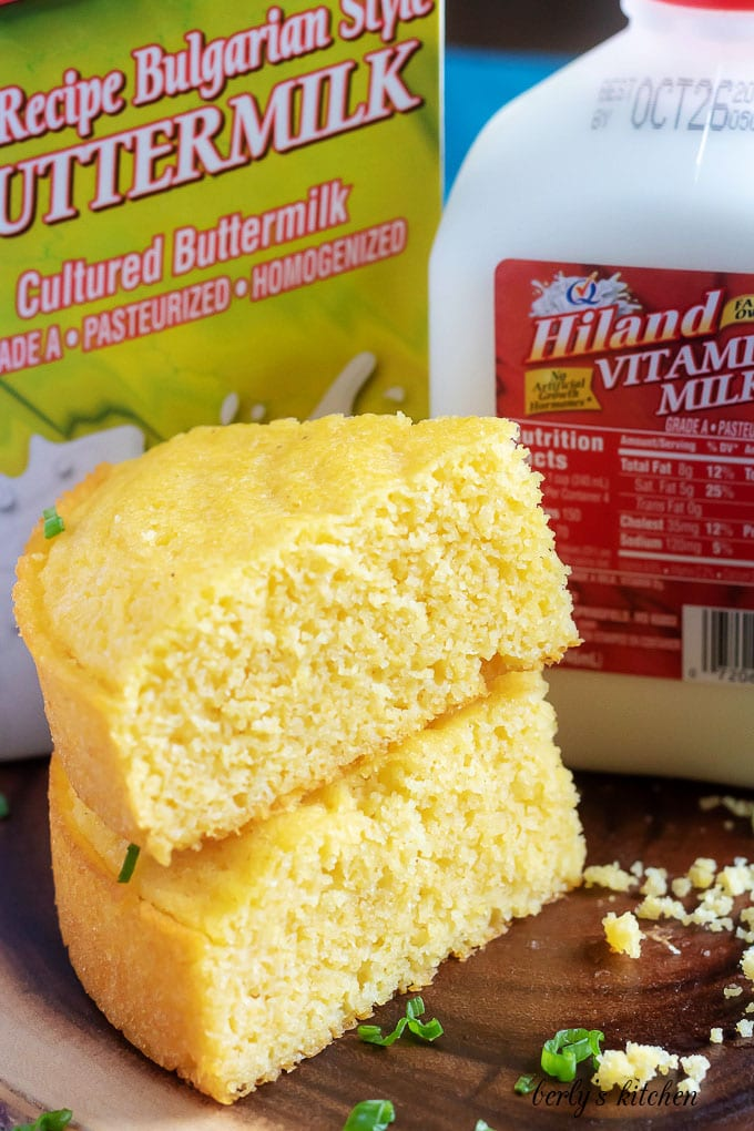 Two pieces of Instant pot cornbread stacked in front of Hiland buttermilk and Hiland whole milk.