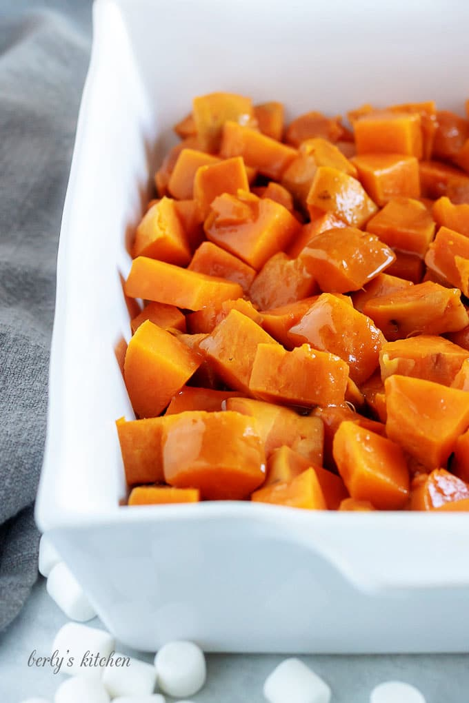 The candied sweet potatoes have been cut into cubes and placed into a large baking dish.