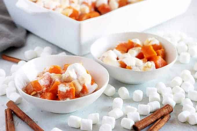 The finished candied sweet potatoes, served in small bowls and topped with marshmallows.
