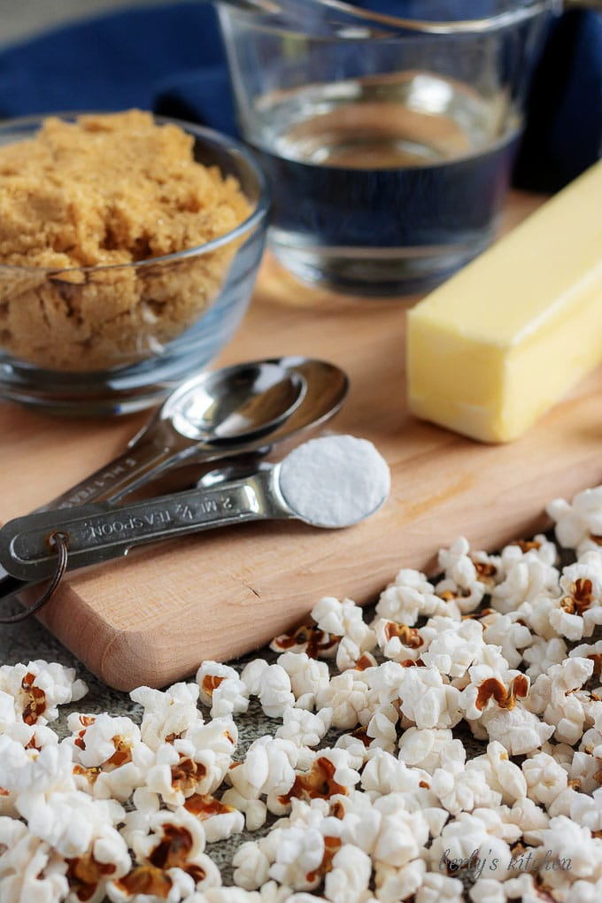 The caramel corn ingredients like butter, brown sugar, and corn syrup sitting on a cutting board sprinkled with popcorn.