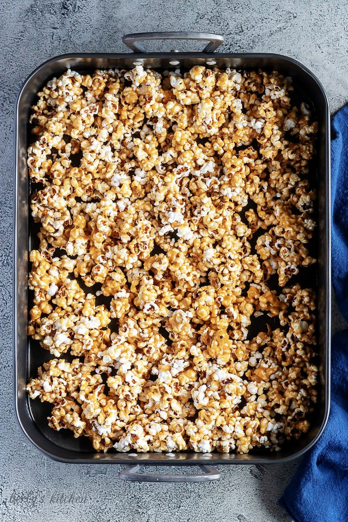 A top-down photo of the caramel corn popcorn spread out in a large roasting pan ready to be baked.