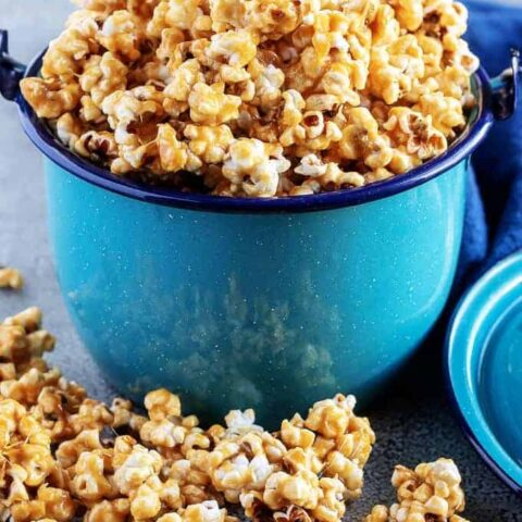 A close-up photo of the finished caramel corn served in a blue metal kettle with the popcorn overflowing the top of the pan.