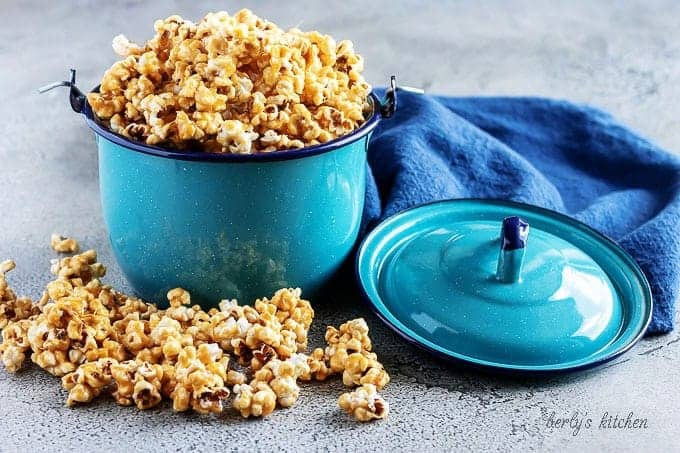 The finished caramel corn popcorn served in a blue kettle, spilling over the top of the kettle.