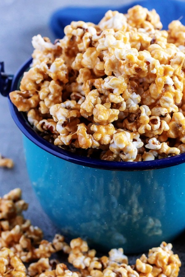 A large picture of the finished caramel corn popcorn, served in a blue tin kettle.