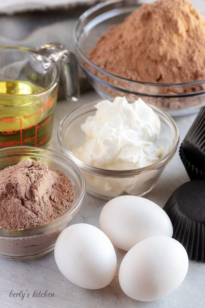 Chocolate cupcakes ingredients like eggs, oil, cake mix, and cream cheese.