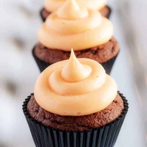 The cream cheese frosting topped cupcakes lined up in a row on a square plate.