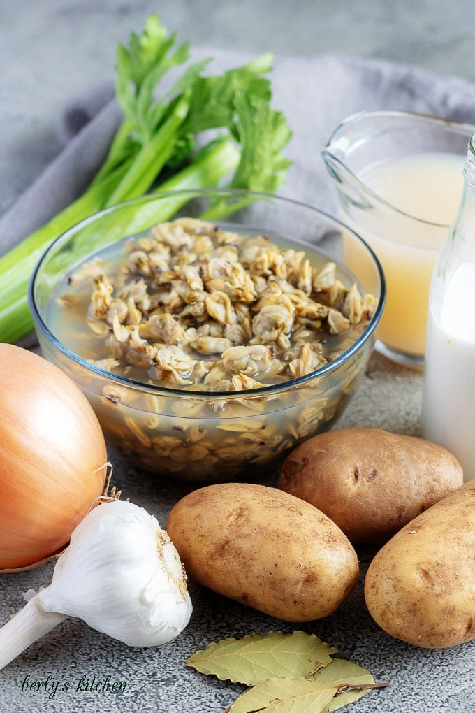 The clam chowder recipe ingredients like clams, onions, garlic, and potatoes.