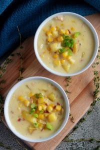 Photo looking down at the corn chowder with bacon, served in white bowls, topped with green onions.