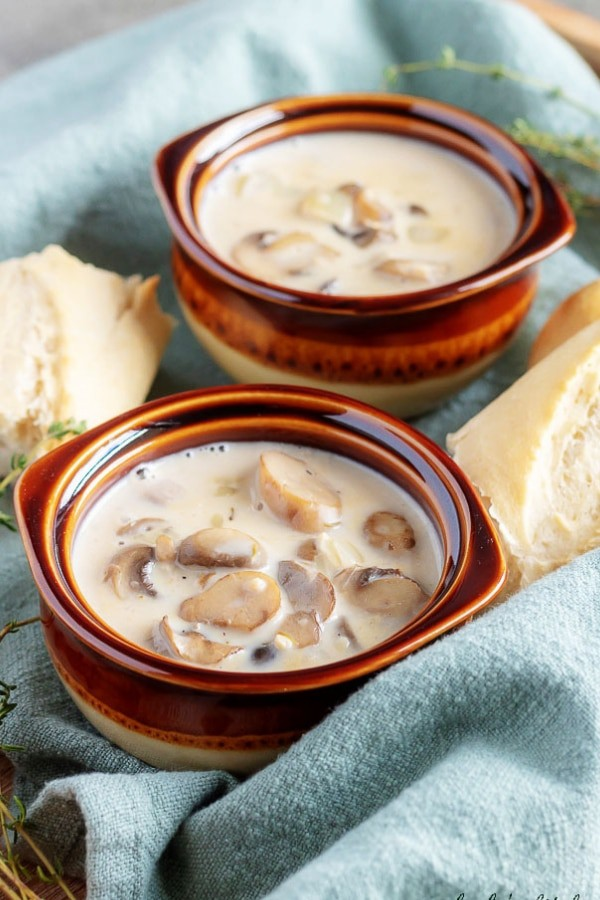 A large picture showing the easy mushroom soup in earthenware bowls served with crusty French bread.