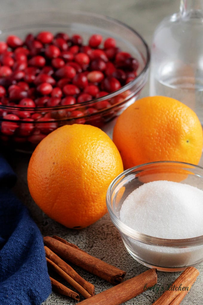 The homemade cranberry sauce ingredients, like sugar, oranges, and cranberries.