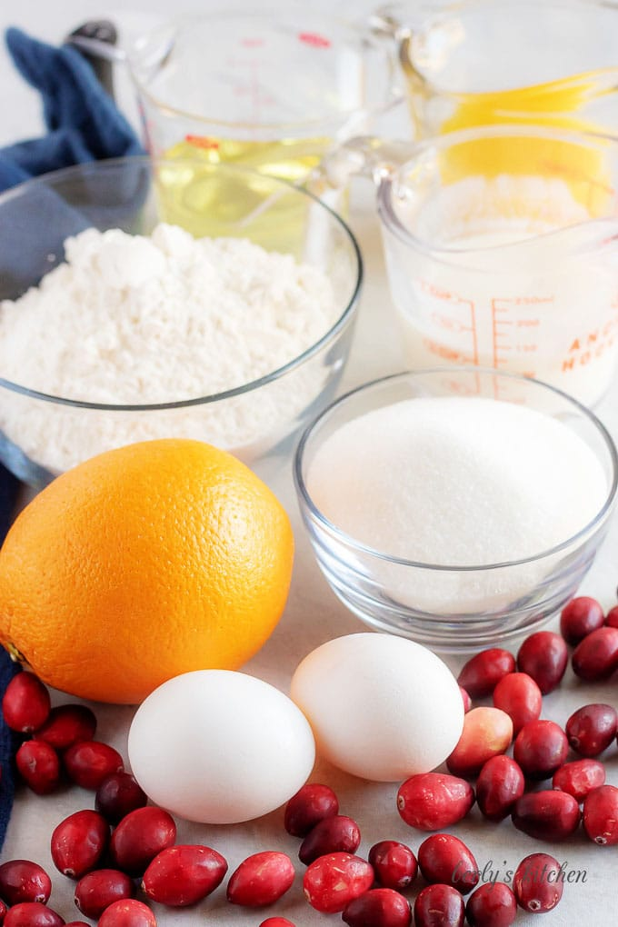 Ingredients used for Orange Cranberry Bread such as eggs, cranberries, fresh orange juice, flour, and sugar.