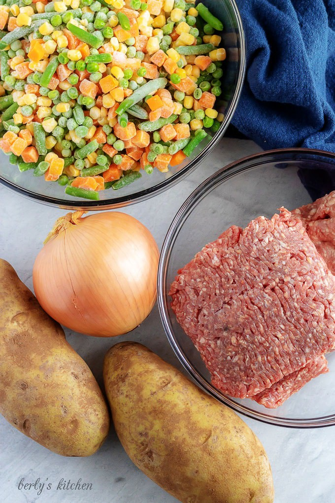 A top-down photo of the shepherd's pie ingredients, like ground beef, lamb, and frozen veggies.