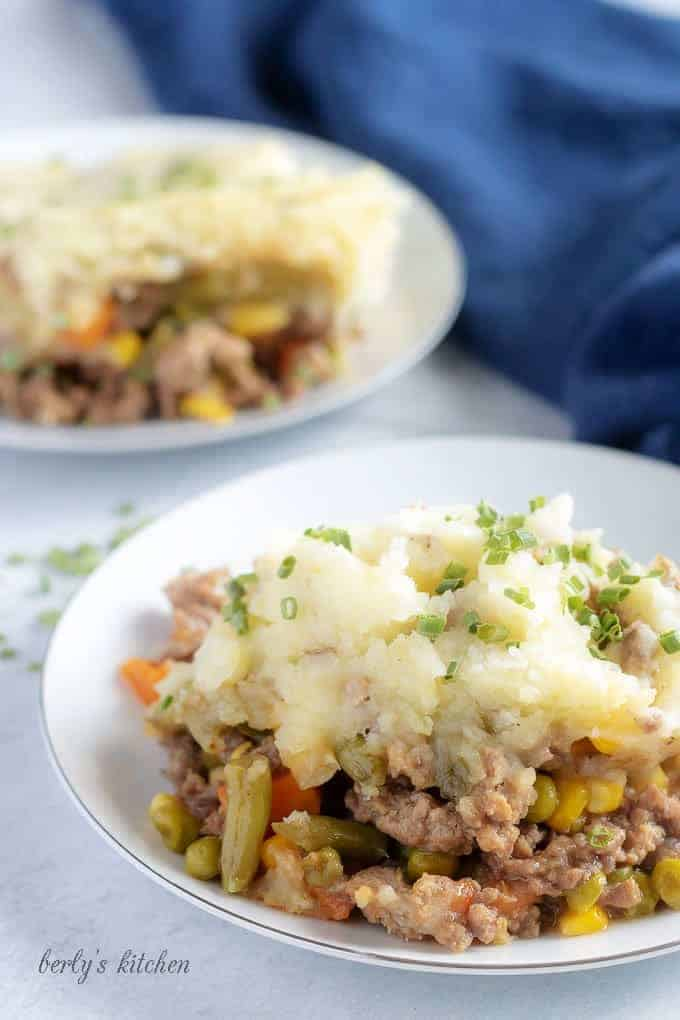 A large picture of the finished shepherd's pie on a plate, garnished with chives and ready to serve.