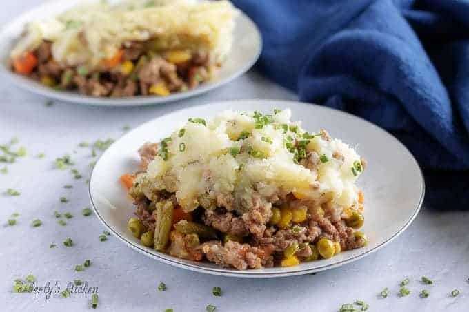 The finished shepherd's pie in a white plate showing the layers of mashed potatoes, veggies, and meat.