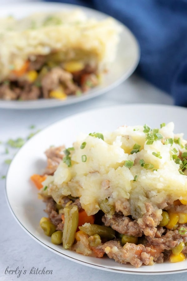 Another large picture of the finished shepherd's pie on a white plate, garnished with chives, and loaded with veggies and meat.