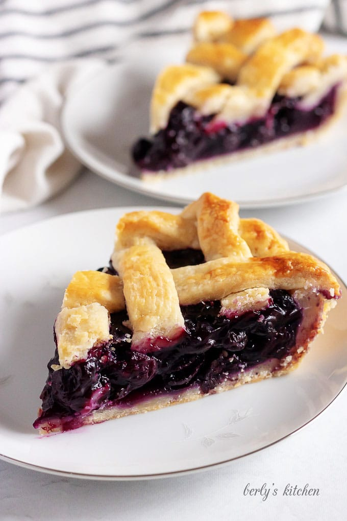 A photo showing two slices of blueberry pie on white plates.