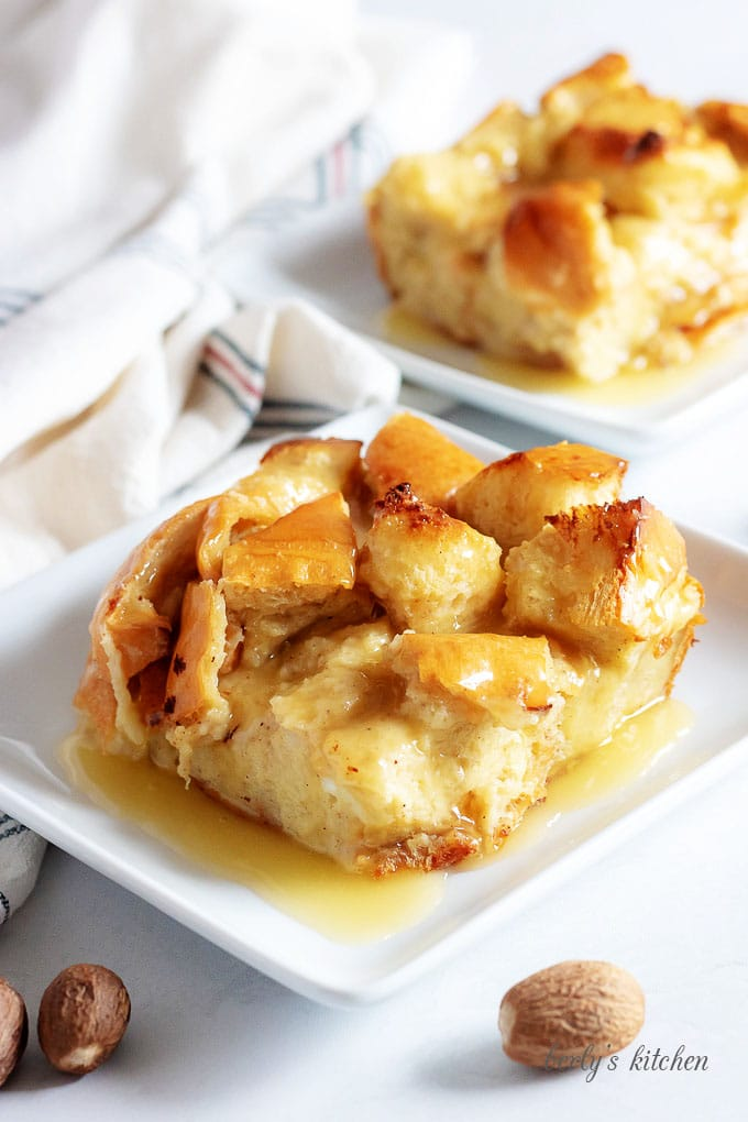 Two pieces of the bread pudding have been placed on square plates and topped with rum sauce.