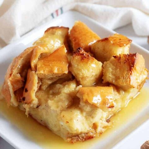 A close-up view of the bread pudding on a square plate accented with fresh nutmeg.