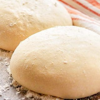 A simple photo of two finished easy pizza dough balls, dusted with flour.