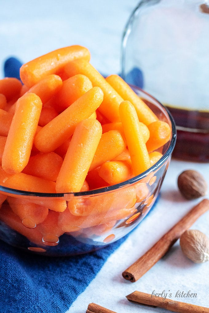 Baby carrots in a glass bowl next to cinnamon sticks, whole nutmeg, and maple syrup.