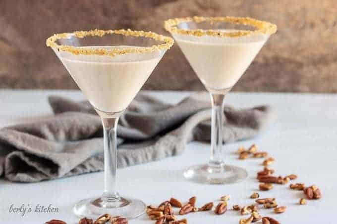 Two pecan pie martinis in martini glasses, rimmed with brown sugar and pecans.