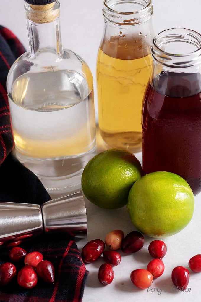 A large photo of the vodka cranberry cocktail ingredients like simple syrup, lime juice, and vodka.