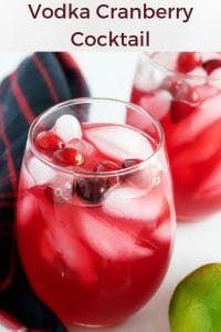 A large picture of the vodka cranberry cocktail served in two stemless wine glasses over ice, garnished with fresh cranberries.
