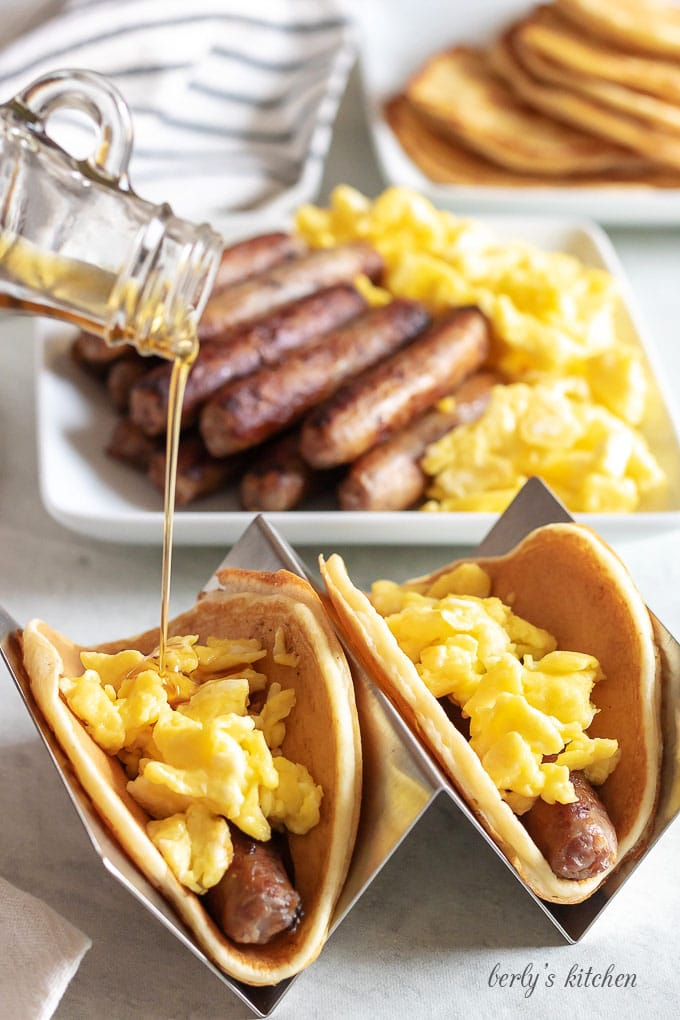 The tacos have been built with sausage and eggs, and topped with maple syrup.