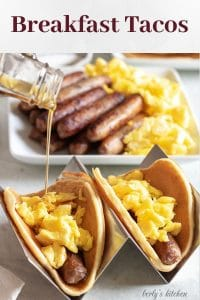 Two finished breakfast tacos with eggs and sausage, drizzled with maple syrup.