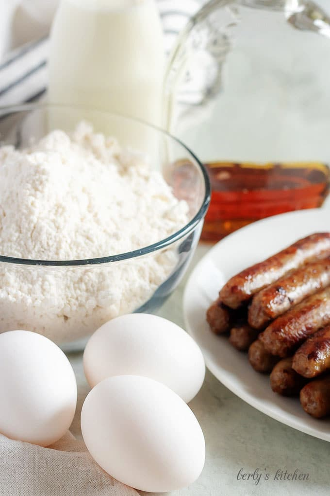 The breakfast taco ingredients like pancake mix, sausage, eggs, and milk.