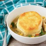 A single serving of the chicken pot pie with biscuits in a white bowl.