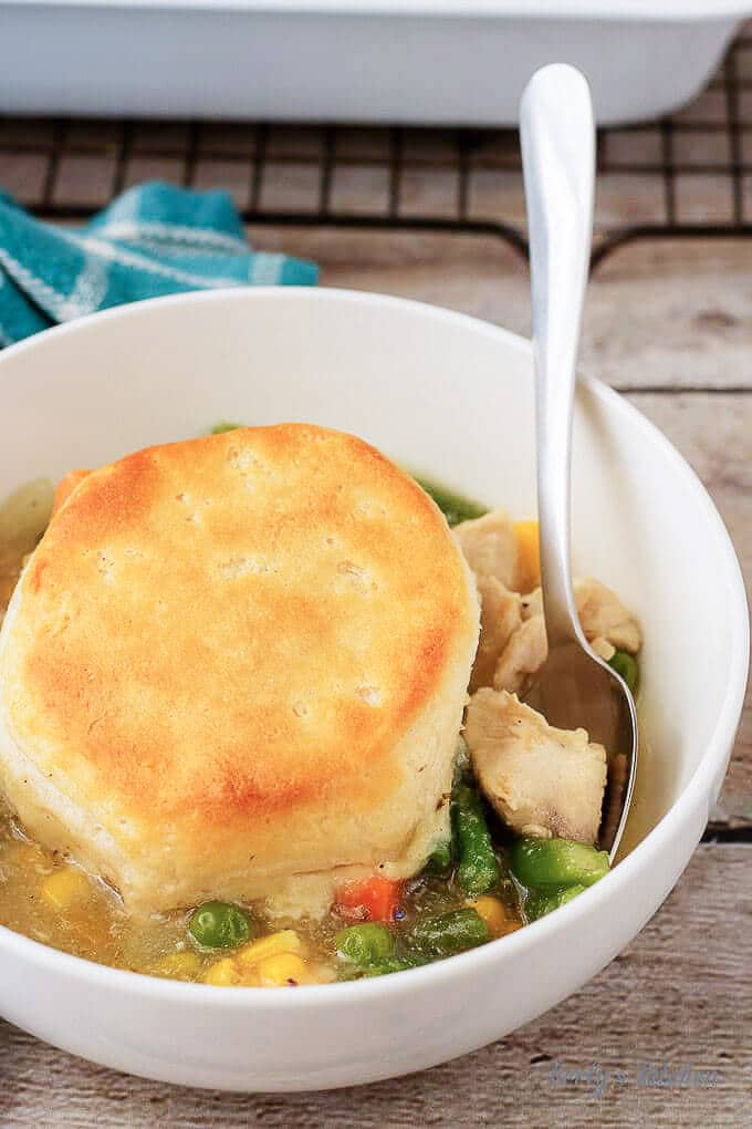 A large photo of the pot pie in white bowl, topped with one golden brown biscuit.