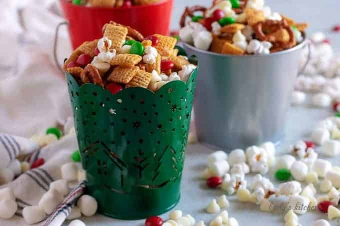 Christmas Chex Mix in festive tins with popcorn and candy scattered around.